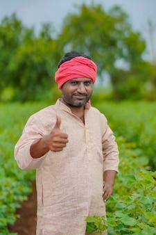 Junger indischer bauer, der im baumwolllandwirtschaftsgebiet steht.