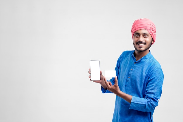 Junger indischer bauer, der karte und smartphone auf weißem hintergrund zeigt.