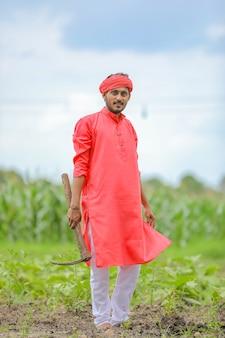 Junger indischer bauer, der landwirtschaftliche ausrüstung in der hand am baumwollfeld hält