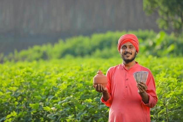 Junger indischer bauer, der lehmschweinbank hält und geld in der hand zeigt