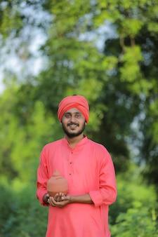 Junger indischer bauer, der lehmschweinbank in der hand hält