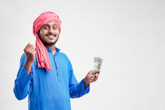 Junger indischer bauer, der mit währung auf weißem hintergrund aufwirft.