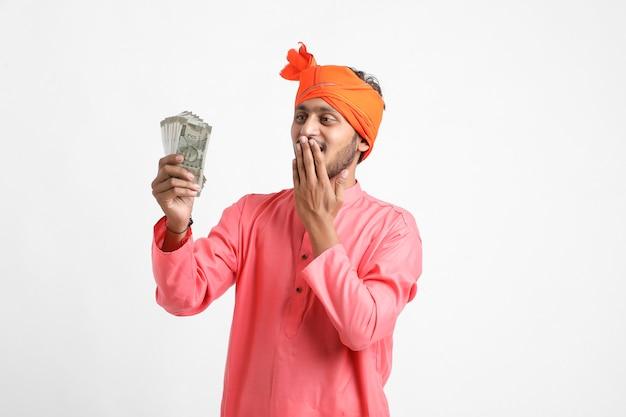 Junger indischer bauer, der mit währung aufwirft