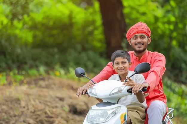 Junger indischer bauer, der sein kind zur schule fallen lässt.