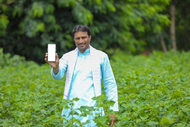 Junger indischer bauer, der smartphone am landwirtschaftsfeld zeigt.