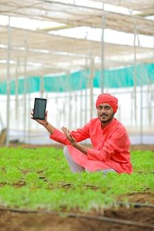 Junger indischer bauer, der smartphone am polyhaus oder am gewächshaus zeigt