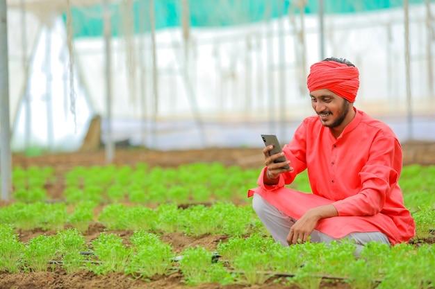 Junger indischer bauer, der smartphone am polyhaus verwendet
