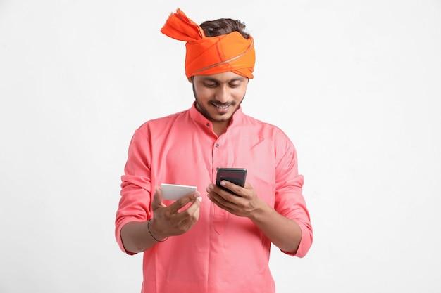 Junger indischer bauer, der smartphone auf weißem hintergrund verwendet.