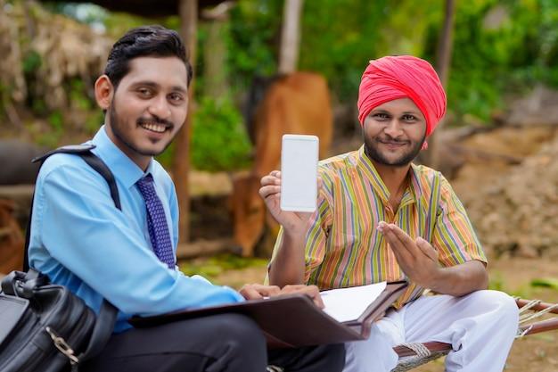 Junger indischer bauer, der smartphone mit bankier oder agronom zeigt