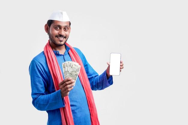 Junger indischer bauer, der smartphone und geld auf weißem hintergrund zeigt.