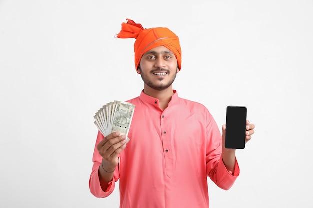 Junger indischer bauer, der smartphone verwendet und geld auf weißem hintergrund zeigt.