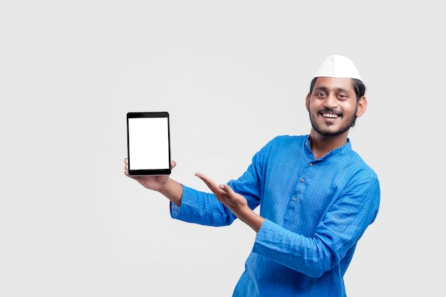 Junger indischer bauer, der smartphone zeigt und ausdruck auf weißem hintergrund gibt.