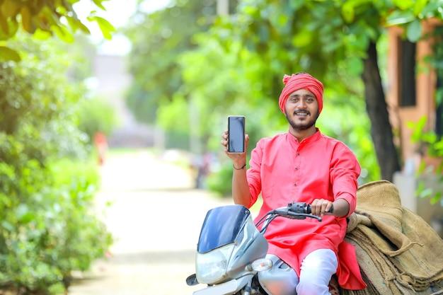 Junger indischer bauer, der smartphone zeigt