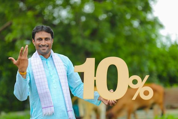 Junger indischer bauer, der zehn prozent brett auf seiner farm zeigt