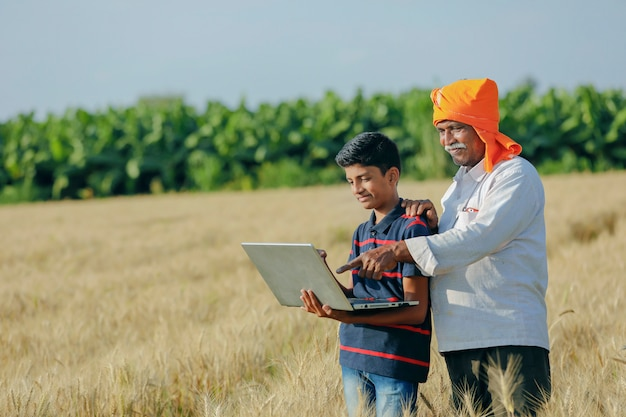 Junger indischer bauer in seinem weizenfeld mit ihrem kind