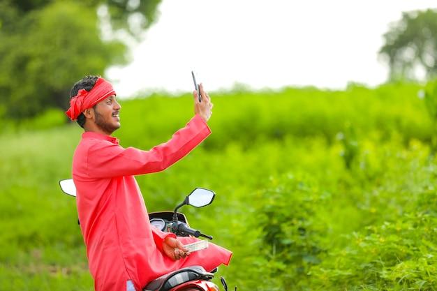 Junger indischer bauer mit geld und telefon