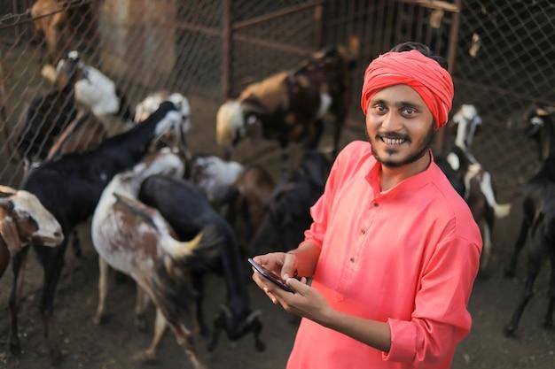 Junger indischer bauer mit smartphone bei ziegenmilchfarm