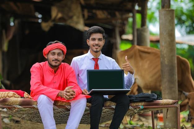 Junger indischer bauer und agronom, der laptopbildschirm zu hause zeigt