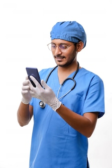 Junger indischer doktor, der smartphone über weißem hintergrund verwendet.