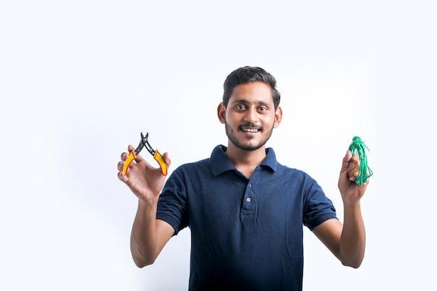 Junger indischer elektriker, der werkzeuge in der hand hält und über weißem hintergrund steht.
