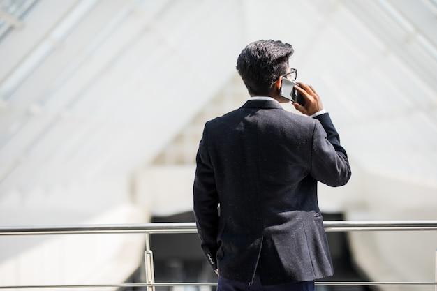 Junger indischer geschäftsmann an einem telefon am telefon