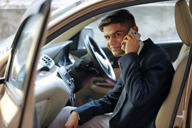 Junger indischer geschäftsmann, der in der seite des autos sitzt und handy verwendet
