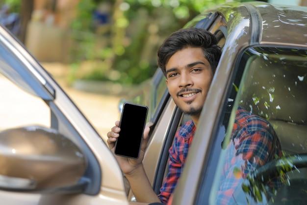 Junger indischer geschäftsmann, der in der seite des autos sitzt und smartphonebildschirm zeigt