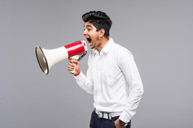 Junger indischer geschäftsmann, der in ein megaphon auf grauer wand ankündigt