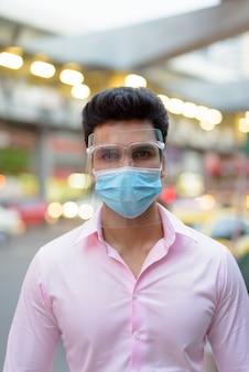 Junger indischer geschäftsmann, der maske und gesichtsschutz in den straßen der stadt im freien trägt