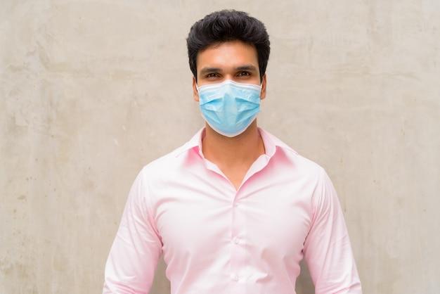 Junger indischer geschäftsmann, der maske zum schutz vor coronavirus-ausbruch im freien trägt