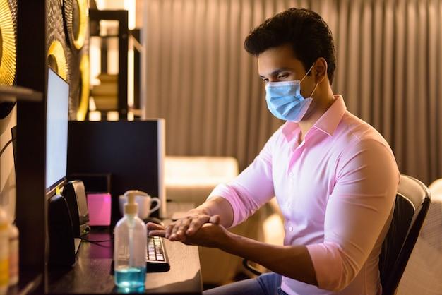 Junger indischer geschäftsmann mit maske, die händedesinfektionsmittel verwendet, während überstunden zu hause während der quarantäne arbeiten
