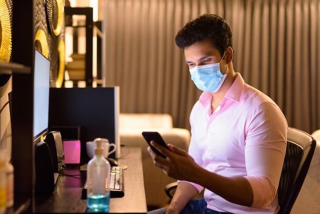 Junger indischer geschäftsmann mit maske, die telefon verwendet, während überstunden zu hause während der quarantäne arbeiten