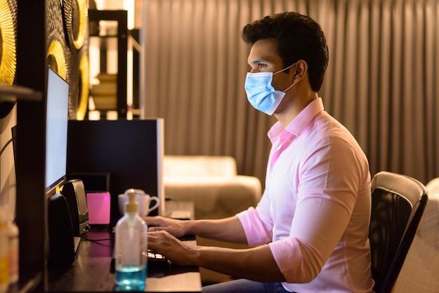 Junger indischer geschäftsmann mit maske, die überstunden zu hause während der quarantäne arbeitet