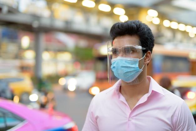 Junger indischer geschäftsmann mit maske und gesichtsschutz, der in den straßen der stadt denkt