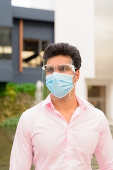 Junger indischer geschäftsmann mit maske und gesichtsschutz, die in der stadt draußen denken