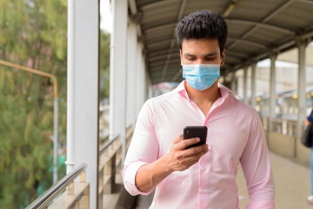 Junger indischer geschäftsmann mit maske unter verwendung des telefons am steg