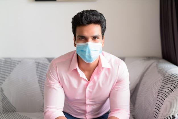 Junger indischer geschäftsmann mit maske zum schutz vor dem ausbruch des koronavirus, der zu hause unter quarantäne bleibt