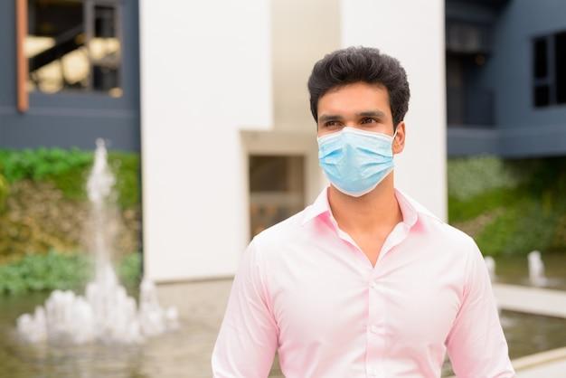 Junger indischer geschäftsmann mit maskendenken in der stadt draußen