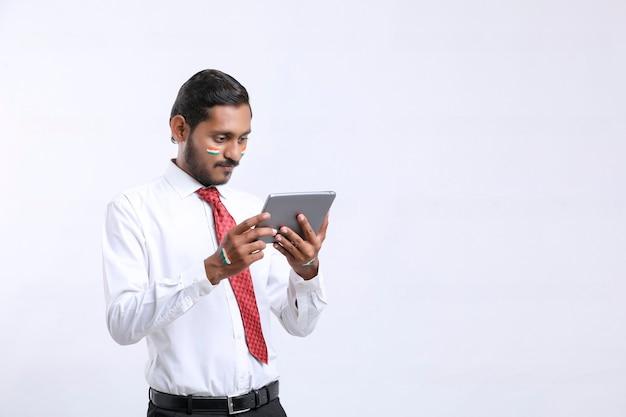 Junger indischer geschäftsmann oder angestellter, der smartphone verwendet.