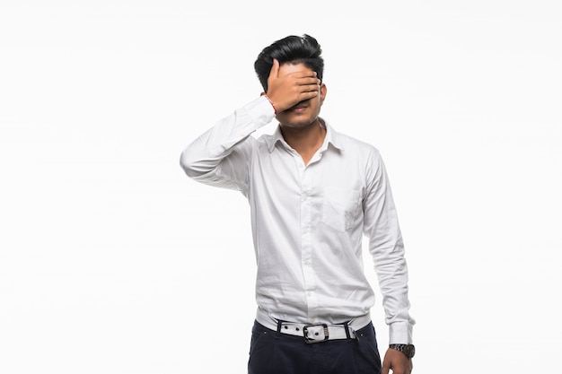 Junger indischer hübscher mann bedecken augen lokalisiert auf weißer wand
