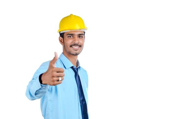 Junger indischer ingenieur mit gelbem schutzhelm und erfolgreicher geste.