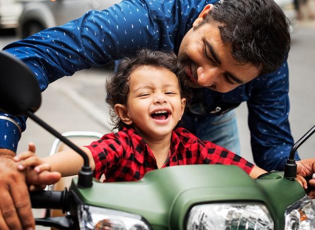 Junger indischer junge, der das motobike reitet