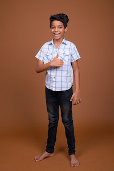 Junger indischer junge, der kariertes hemd gegen braunen hintergrund trägt