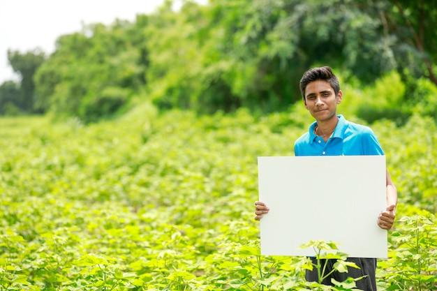 Junger indischer junge, der leeres plakat am feld hält