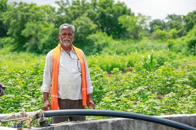 Junger indischer landwirt, der am feld arbeitet