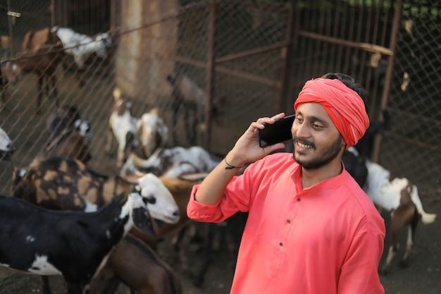 Junger indischer landwirt, der auf smartphone bei ziegenmilchfarm spricht