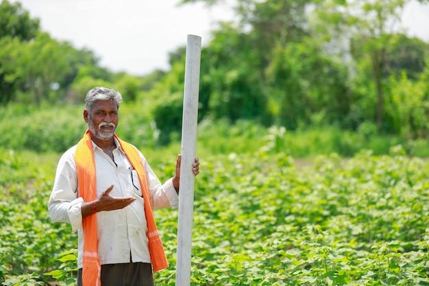 Junger indischer landwirt, der rohr am baumwollfeld hält.