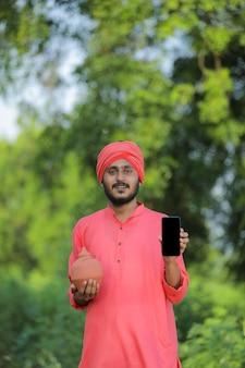 Junger indischer landwirt, der sparschwein der ton hält und smartphone in der hand zeigt