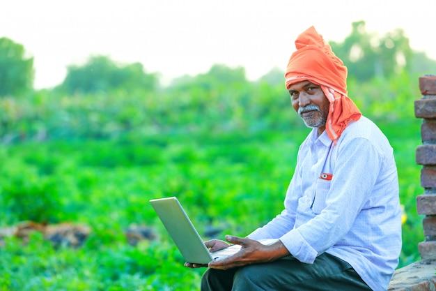 Junger indischer landwirt mit laptop am feld