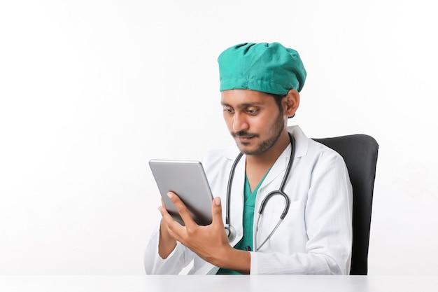 Junger indischer männlicher arzt mit smartphone in der klinik.